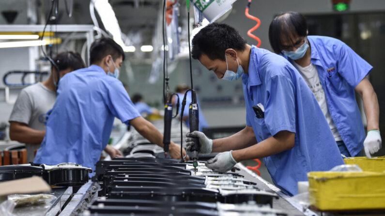 Los trabajadores producen piezas de lavadoras en una fábrica en Nanjing, en la provincia oriental china de Jiangsu, el 16 de agosto de 2021. (STR/AFP)