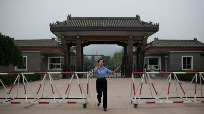 Una mujer policía se acerca para detener la toma de fotografías en la entrada de la prisión de Qincheng, en las afueras de Beijing, el 12 de septiembre de 2013. (Ed Jones/AFP a través de Getty Images)