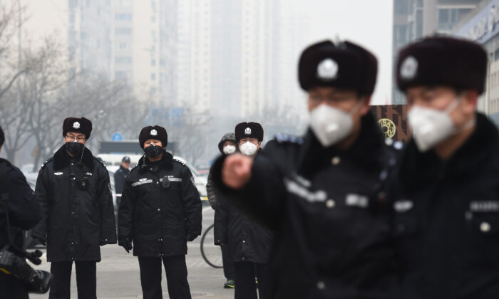Varios policías hacen guardia en Beijing el 22 de diciembre de 2015 en el exterior del Tribunal Popular Intermedio nº 2, donde el abogado de derechos humanos Pu Zhiqiang estaba siendo condenado. (Greg Baker/AFP vía Getty Images)