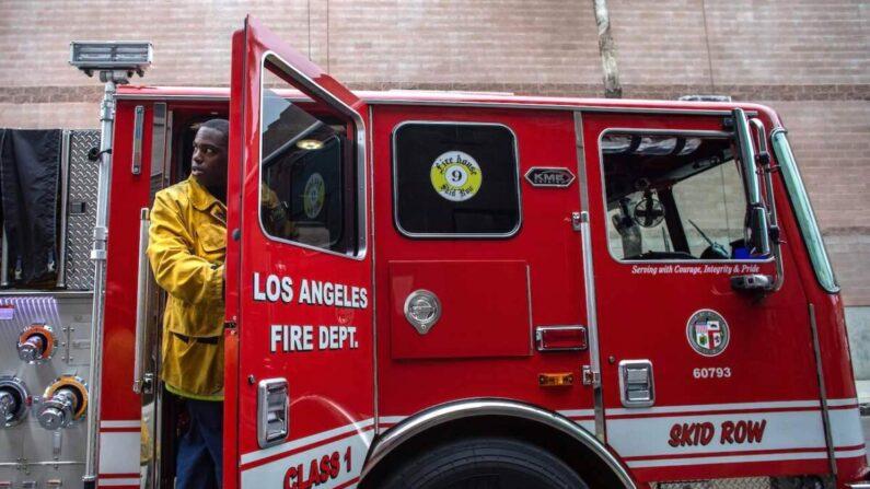 Un bombero en período de prueba deja un camión de bomberos en Skid Row en el centro de Los Ángeles, California, el 12 de abril de 2020. (Apu Gomes/AFP a través de Getty Images)