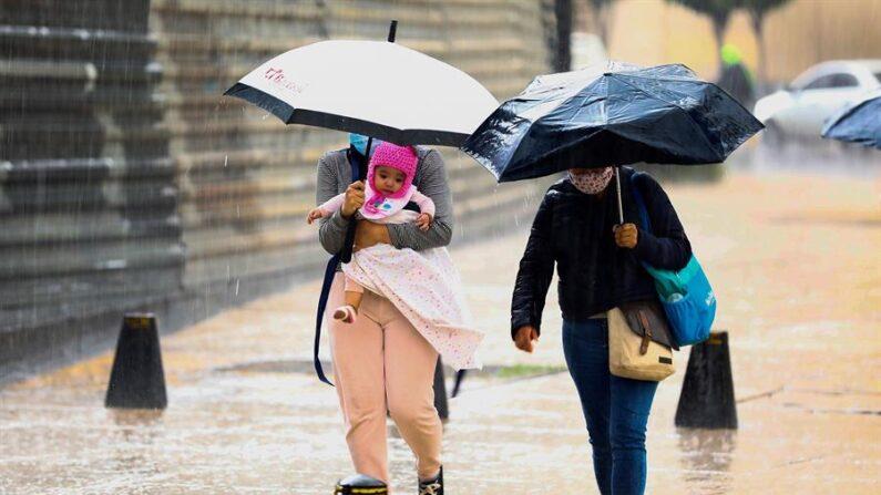 Fotografía de archivo de una persona resguardándose de la lluvia. EFE/Carlos Ramírez