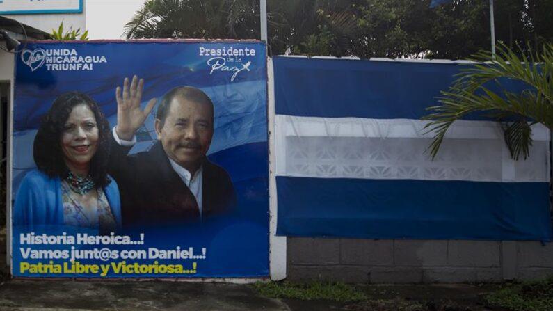 Fotografía de archivo de una pancarta política con la imagen de la formula presidencial del presidente de Nicaragua, Daniel Ortega (d), y su esposa, la vicepresidenta Rosario Murillo (i), junto a una Bandera de Nicaragua en Managua (Nicaragua). EFE/Jorge Torres