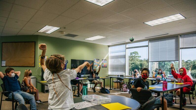 Se ve a los niños usando mascarillas en cumplimiento de una orden en una actividad en clase en la Academia Xavier en Houston, Texas, el 23 de agosto de 2021. (Brandon Bell/Getty Images)