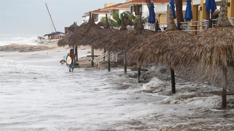 Fotografía de archivo en la que se observa a un hombre caminando en una playa frente a grandes olas en el puerto de Mazatlán del estado mexicano de Sinaloa. EFE