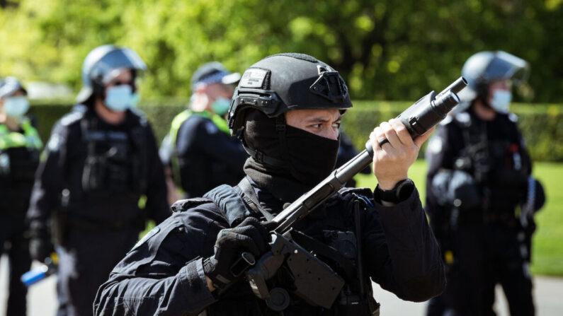 Un policía antidisturbios blande un arma mirando hacia adelante a los manifestantes cerca del Santuario del Recuerdo, en Melbourne, Australia, el 22 de septiembre de 2021. (Darrian Traynor/Getty Images)
