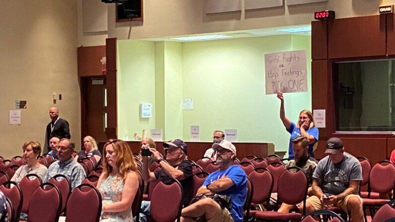 Una mujer sostiene un cartel mientras el miembro de la junta directiva Jeff Morse habla en la reunión de la junta de las escuelas públicas del condado de Loudoun en Virginia el 11 de agosto de 2021. (Terri Wu/The Epoch Times)