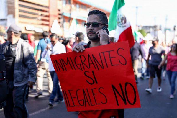 """Rodrigo Melgoza, residente de Tijuana, sostiene un letrero que dice """"inmigrantes sí, ilegales no"""" durante una protesta contra la caravana de migrantes de Centroamérica en Tijuana, México, el 18 de noviembre de 2018. (Charlotte Cuthbertson/La Gran Época)"""