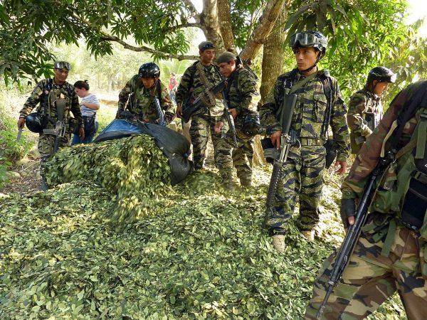 """Oficiais de drogas esvaziam sacos de folhas secas de coca depois de encontrar um laboratório clandestino na floresta tropical do vale Apurimac, no sudeste do Peru, em 21 de agosto de 2010. Segundo as autoridades locais, a guerrilha do Sendero Luminoso começou a """" terras desapropriadas """", principalmente na área conhecida como Vraem (vales dos rios Ene e Apurímac, dos departamentos de Ayacucho, Cusco, Junín e Huancavelica), para cultivar coca e depois produzir cocaína (CARLOS MANDUJANO / AFP / Getty Images)"""