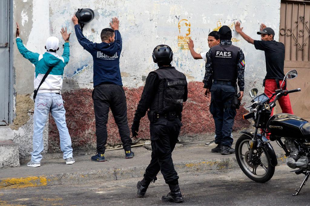 Membros do Grupo de Forças Especiais da Polícia Nacional Bolivariana (FAES) detêm um grupo de homens durante uma operação no bairro de Petare, em Caracas, em 25 de janeiro de 2019 (LUIS ROBAYO / AFP / Getty Images)