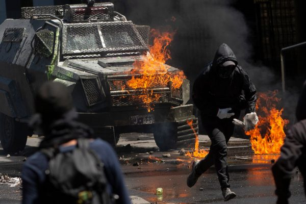 Manifestantes enfrentam a polícia de choque durante um protesto em Santiago, Chile, em 21 de outubro de 2019. (CLAUDIO REYES / AFP via Getty Images)