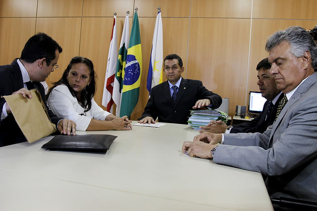 """A médica cubana Ramona Matos Rodríguez é acompanhada por seu advogado, Fabricio Medeiros (à esquerda) e deputados federais Ronaldo Caiado (d) e Mendonça Filho (2-d) no prédio do Ministério do Trabalho, onde chegou para denunciar irregularidades no programa do governo federal """"Mais Médicos"""", em Brasília, em 10 de fevereiro de 2014 (BETO BARATA / AFP / Getty Images)"""