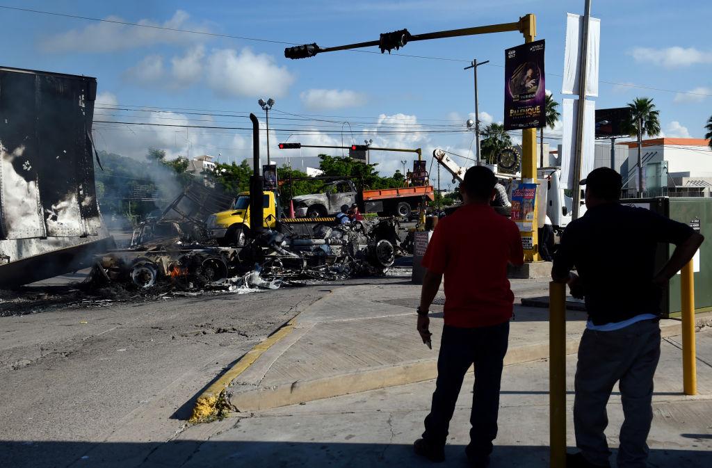 Dois homens olham para os veículos queimados depois que homens armados pesadamente armados travaram uma batalha total contra as forças de segurança mexicanas em Culiacan, estado de Sinaloa, México, em 18 de outubro de 2019 (ALFREDO ESTRELLA / AFP através da Getty Images)