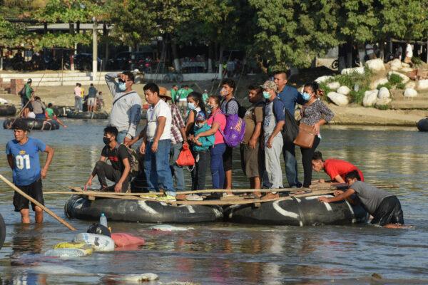 Personas cruzan el río Suchiate en una balsa desde Guatemala hasta Ciudad Hidalgo, México, el 18 de enero de 2021, cuando se espera la llegada de una nueva caravana de migrantes, en su mayoría de hondureños que se dirigen a Estados Unidos. (Isaac Guzman/AFP vía Getty Images)